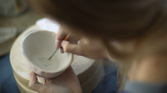young woman making handmade ceramics in her pottery workshop, small business concept - artist stock videos & royalty-free footage
