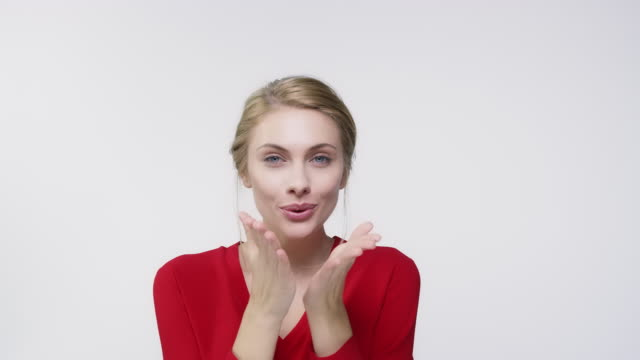 Young woman making heart shape and blowing kiss