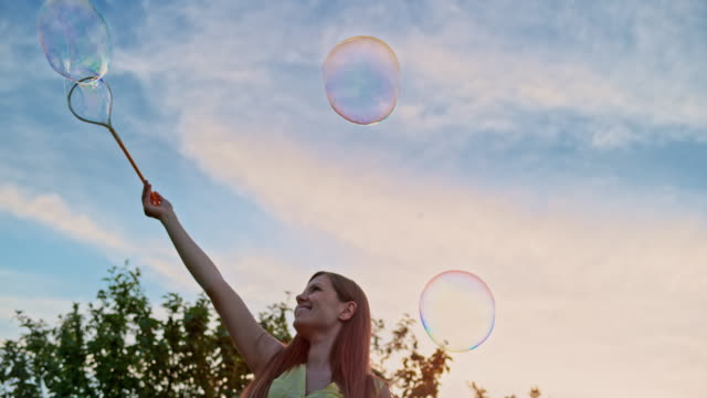 SLO MO Young woman making large soap bubbles and smiling