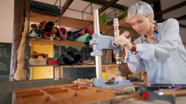 young woman making leather bracelets at the workshop while using hammer, nails and hole puncher - hammer stock videos & royalty-free footage