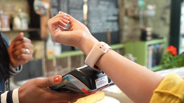 young woman making payment with smart watch - retail stock videos & royalty-free footage