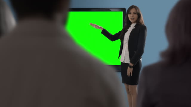 Young woman making presentation in office against green screen