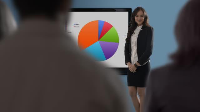 vídeos de stock e filmes b-roll de young woman making presentation in office - saia