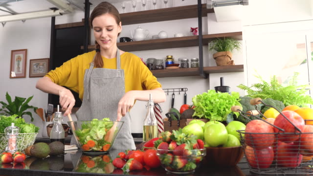 young woman making salad in the kitchen - healthy eating stock videos & royalty-free footage