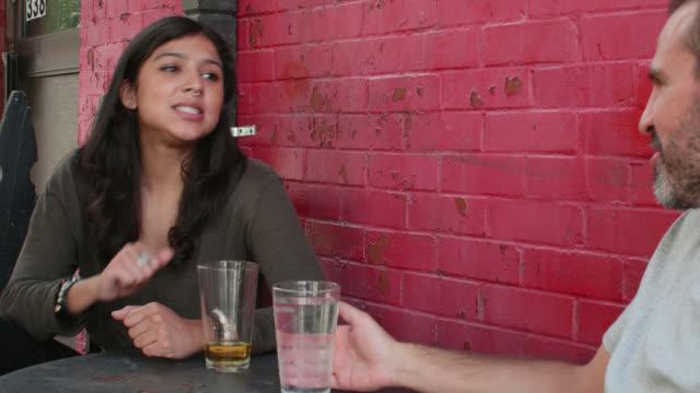 stockvideo's en b-roll-footage met young woman making salient points to man at outdoor café - hanenkam haardracht