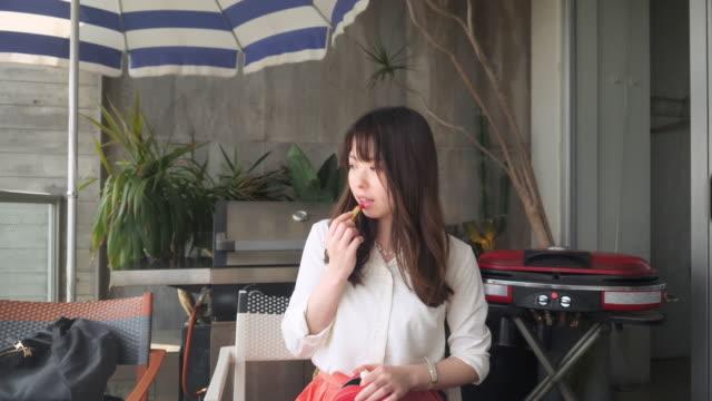 カフェバルコニーで昼食後に作り上げる若い女性 - 神奈川県点の映像素材/bロール