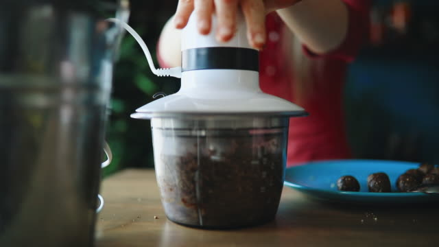 vidéos et rushes de jeune femme faisant des morceaux crus crus végétaliens doux - aliment cru