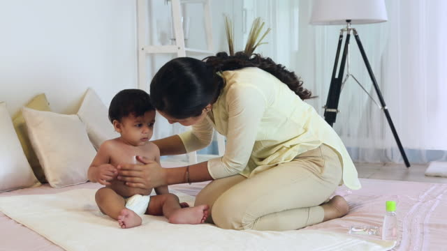 vidéos et rushes de young woman massaging her baby son - massage room