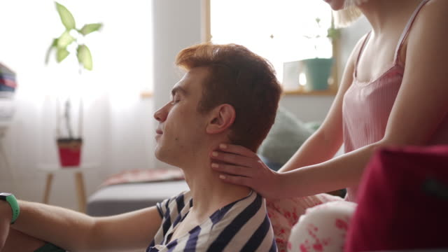 young woman massaging her boyfriend's neck at home early in the morning - neckache stock videos & royalty-free footage