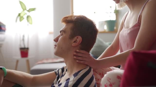 vídeos de stock e filmes b-roll de young woman massaging her boyfriend's neck at home early in the morning - dor no pescoço