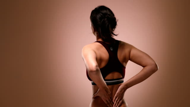 ms young woman massaging her painful neck while standing against pink background / new delhi, delhi, india - bra stock videos & royalty-free footage