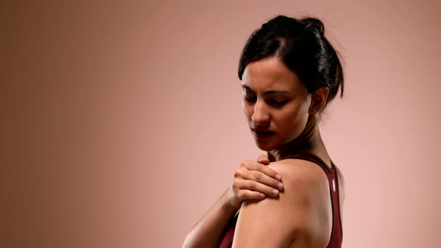 CU Young woman massaging her painful shoulder against pink background / New Delhi, Delhi, India