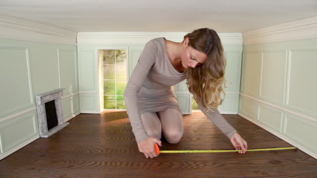 Young woman measuring floor in small room