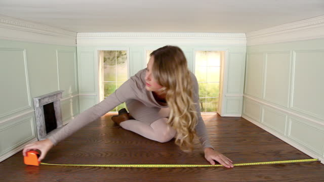 young woman measuring floor in small room - dollhouse stock videos & royalty-free footage