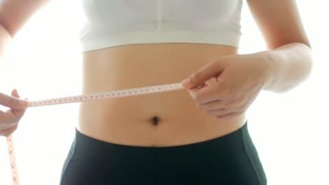 若い女性が彼女の腰をタップを測定する場合の測定 - ほっそりした点の映像素材/bロール