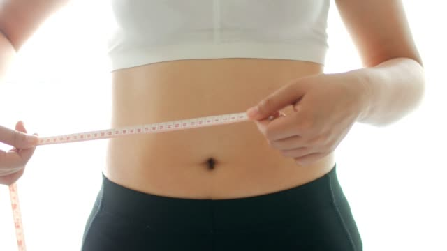 young woman measuring her waist with measuring tap - dieting stock videos & royalty-free footage