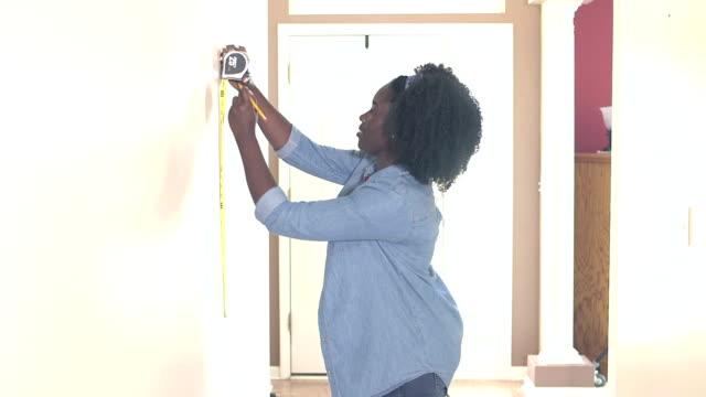vídeos de stock, filmes e b-roll de jovem mulher medir a parede para pendurar quadro - pendurar