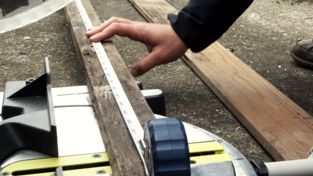 A young woman measuring wood and cutting.