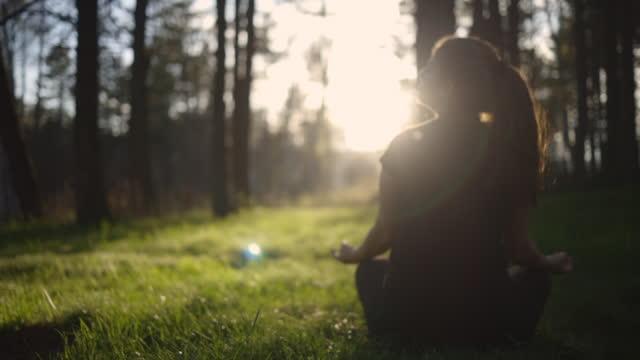 stockvideo's en b-roll-footage met young woman meditating at sunset - lotuspositie
