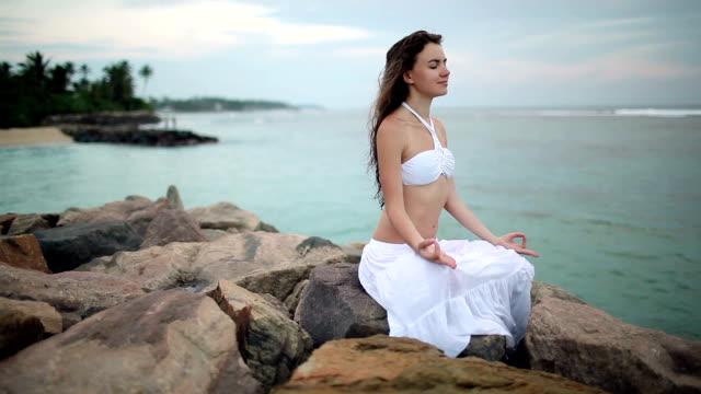 vídeos de stock, filmes e b-roll de jovem mulher meditating na praia - olhos fechados