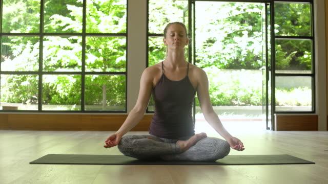 vídeos y material grabado en eventos de stock de young woman meditating by herself - centro de yoga