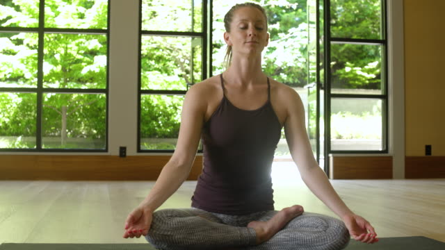 young woman meditating by herself - maglietta senza maniche video stock e b–roll