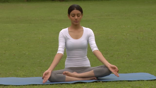 ms, young woman meditating in park, chattarpur, new delhi, india - lotussitz stock-videos und b-roll-filmmaterial