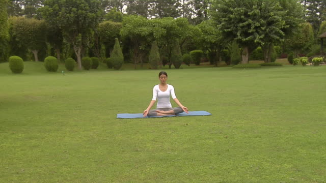 ws, zo,  young woman meditating in park, chattarpur, new delhi, india - schneidersitz stock-videos und b-roll-filmmaterial