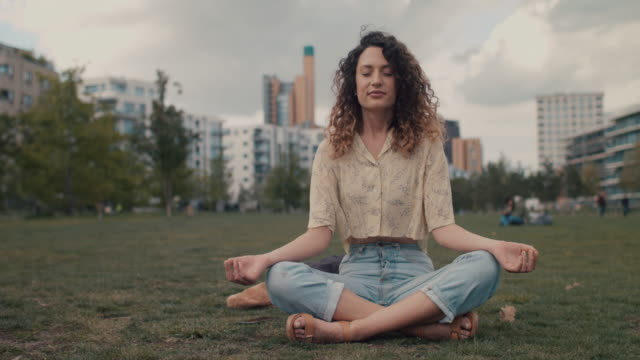 young woman meditating in park in central berlin - enjoyment stock videos & royalty-free footage