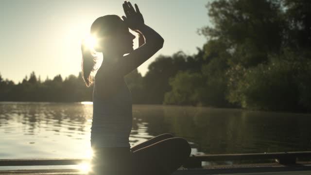 vidéos et rushes de a young woman meditating on a pier at sunrise - assis en tailleur