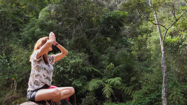 stockvideo's en b-roll-footage met young woman meditating on a rock in a lush forest - in kleermakerszit