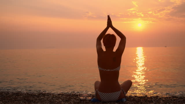 ds young woman meditating on the beach - lotus position stock videos & royalty-free footage
