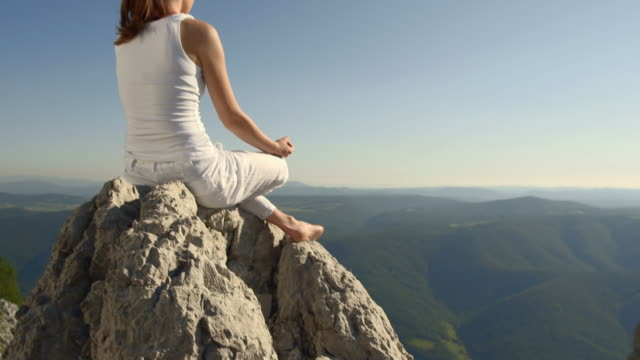 HD: Young Woman Meditating On The Cliff