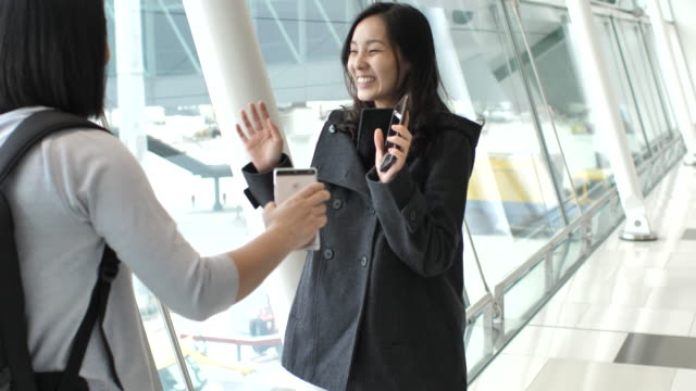 young woman meet with friend arriving in the airport, embracing - greeting stock videos & royalty-free footage