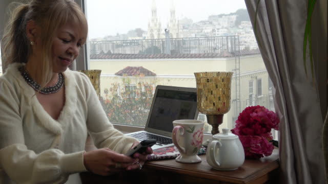 Young Woman Mobile Networking in Home Office with City Views