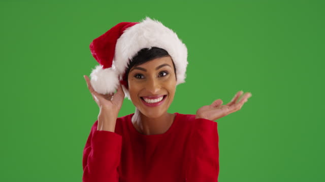young woman modeling santa claus hat, smiling and laughing on green screen - santa hat stock videos & royalty-free footage