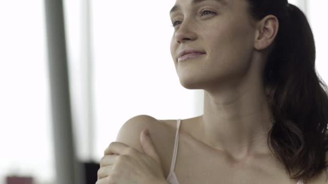 vidéos et rushes de young woman moisturizing shoulder - human body part
