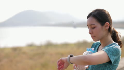 young woman monitoring her running performance on smartwatch - one mid adult woman only stock videos & royalty-free footage