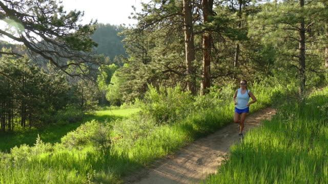Young woman morning trail run Bear Creek Colorado Rocky Mountains