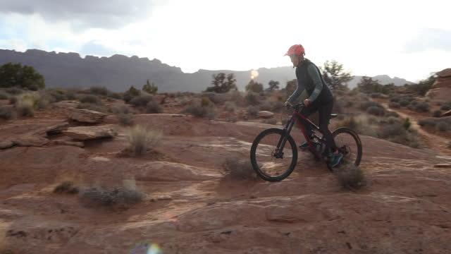 young woman mountain bikes along faint desert pathway - moab utah stock videos & royalty-free footage