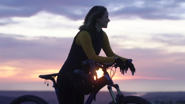 ms young woman mountain biking at sunset - riposarsi video stock e b–roll