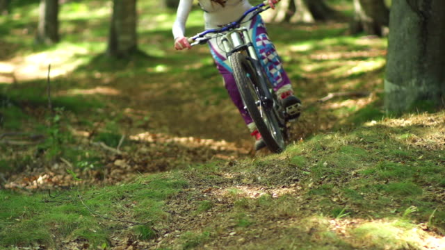 young woman mountain biking through a forest - mountain bike stock videos and b-roll footage