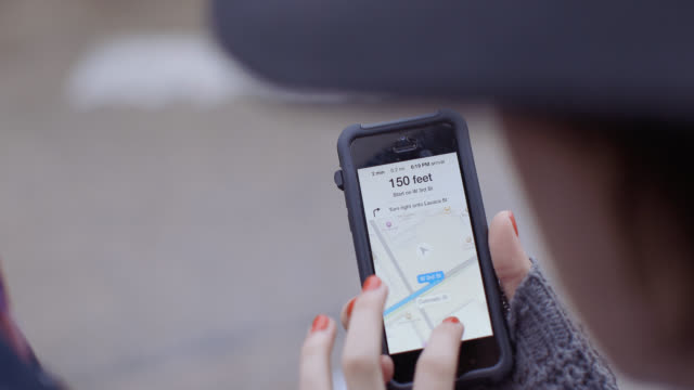 vidéos et rushes de young woman moves map around with her fingers on smartphone touchscreen - application mobile