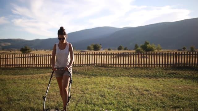 giovane donna falciare il prato fuori dalla sua casa - tosaerba video stock e b–roll