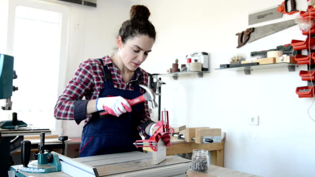 young woman nailing wood plates with sound/audio - hammer stock videos and b-roll footage