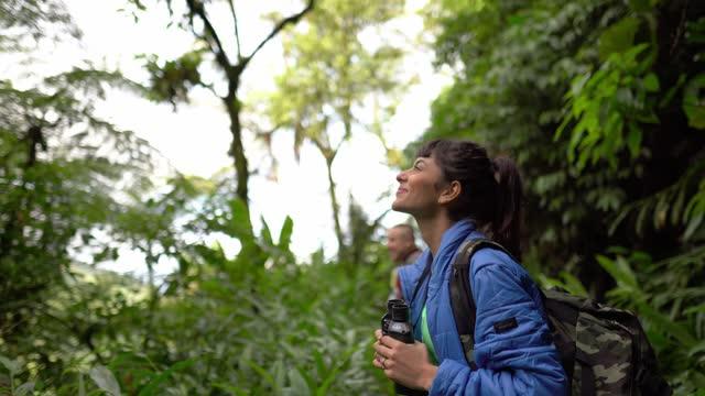 vídeos de stock, filmes e b-roll de jovem observando usando um binóculo em uma floresta - ecoturismo