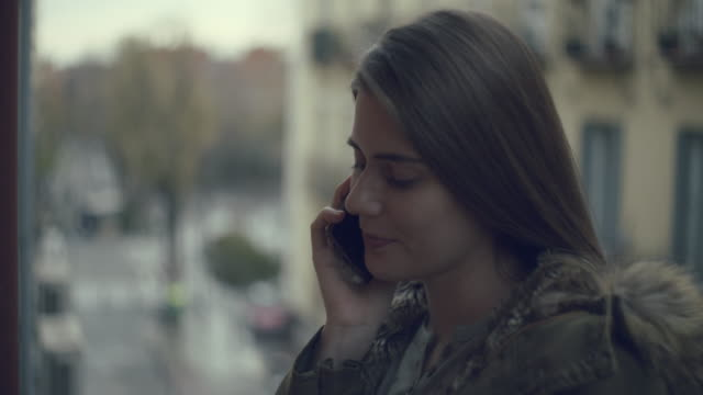Young woman on a balcony talking on the phone.