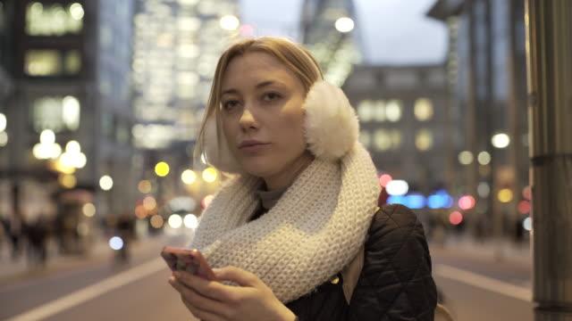 a young woman on a city street at night. - ohrenschützer stock-videos und b-roll-filmmaterial