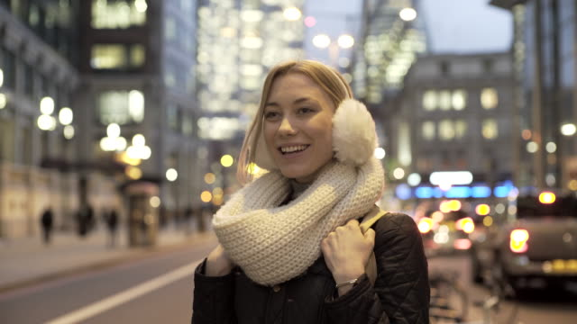 vídeos de stock, filmes e b-roll de a young woman on a city street at night. - protetor de ouvido