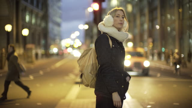A young woman on a city street at night.